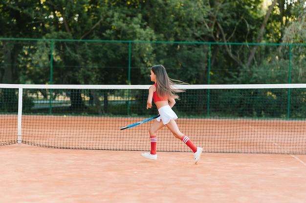 Kind tennissen op buitenbaan. meisje met tennisracket en bal in sportclub. actieve oefening voor kinderen