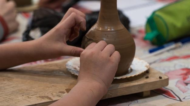 Kind tijdens het verfraaien van de kleipot. pottenbakkerij voor kinderen
