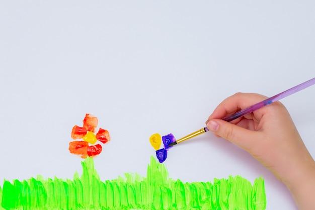 Kind trekt bloemen door aquarellen op wit papier. bovenaanzicht. kinder en aarde dag concept.