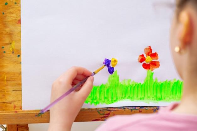 Kind trekt bloemen door aquarellen op wit papier op een ezel. kinder en aarde dag concept.