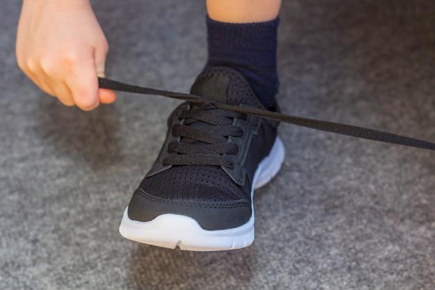 Kind trok een paar sneakers aan. de benen van de jonge jongen in textiel mode zwarte sneakers. trendy casual kinderkleding en street fashion. detailopname