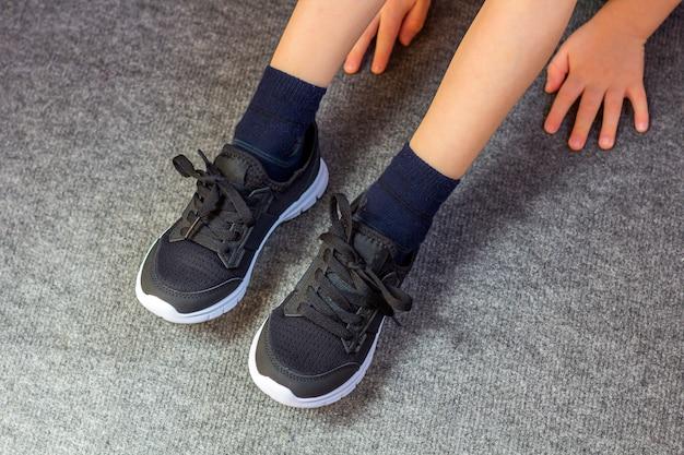 Kind trok een paar sneakers aan. de benen van de jonge jongen in textiel mode zwarte sneakers.