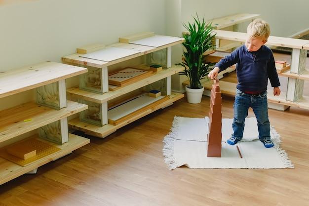 Kind van 3 jaar, student van een montessori pedagogiek school, het plaatsen van het laatste stuk van een roze toren met blokken