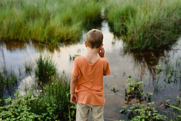 Kind van achter het kijken naar het kalme water van een meer