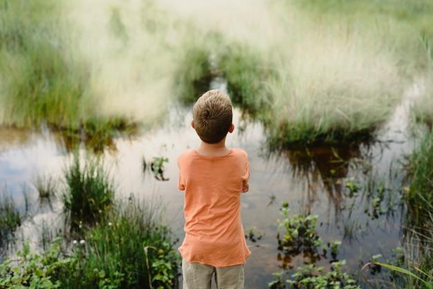Kind van achteren kijken naar het kalme water van een meer