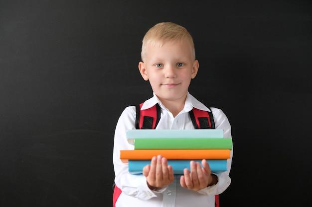 Kind van basisschool met boeken en tas op blackboard