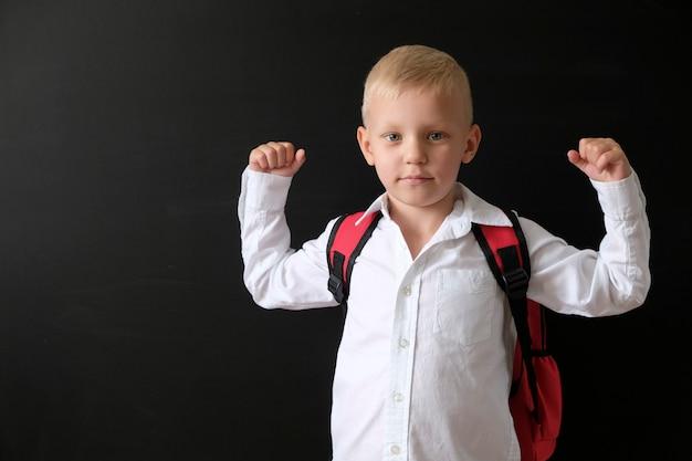 Kind van basisschool met tas op blackboard.