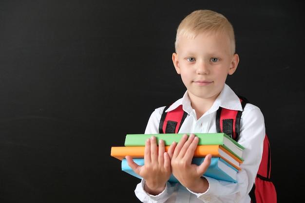 Kind van de lagere school met boeken en tas.