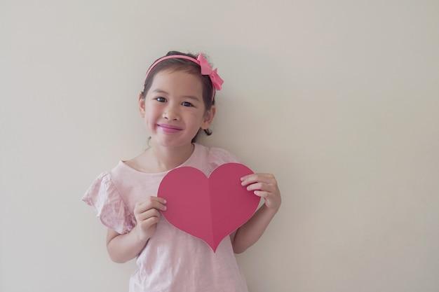 Kind van gemengd ras met een groot rood hart, hartgezondheid, donatie, gelukkige vrijwilligersliefdadigheid, sociale verantwoordelijkheid, wereldhartdag, wereldgezondheidsdag, werelddag voor geestelijke gezondheid, welzijn, hoopconcept
