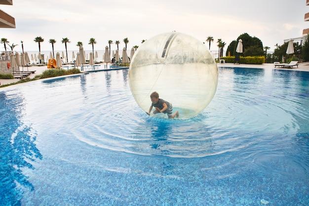 Kind veel plezier in grote plastic ballon op het water van het zwembad op het zomerverblijf. kleine jongen binnen grote opblaasbare transparante bal rennen en plezier maken.