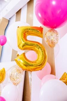 Kind verjaardagsdecoratie jaar nummer wit roze lucht ballonnen grote gouden bal van nummer vijf op partij decor achtergrond heldere begroeting zone voor een vakantie verjaardag verjaardag