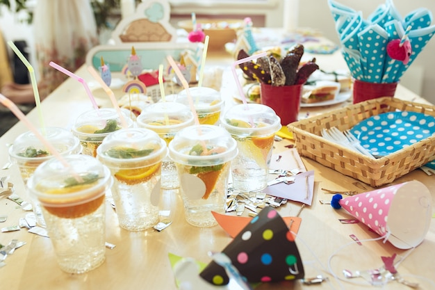 Kind verjaardagsdecoratie. roze tafelsetting van bovenaf met taarten, drankjes en feestgadgets.