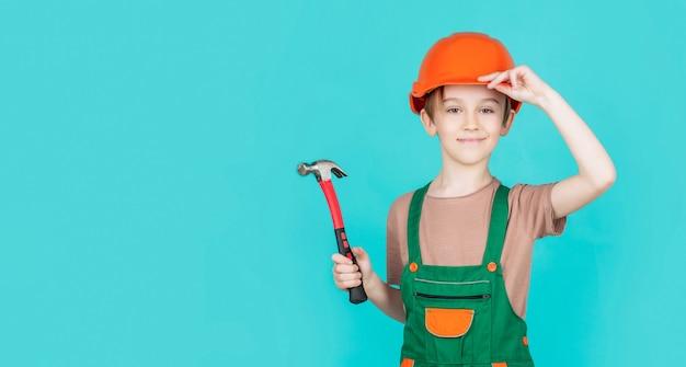 Kind verkleed als werkmanbouwer. kleine jongen die helm draagt. portret kleine bouwer in bouwvakker hamer. kind bouwhelm, bouwvakker. hamer hameren