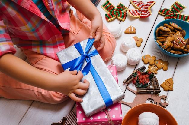 Kind versieren cadeautjes in de voorbereiding van kerstmis