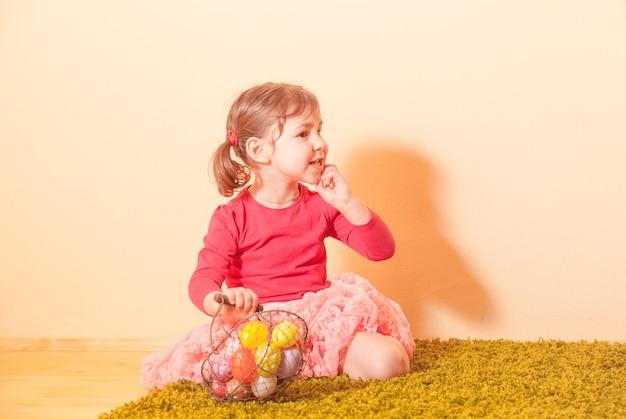 Kind verzamelt kleurrijke eieren in de manden tijdens het zoeken naar paaseieren