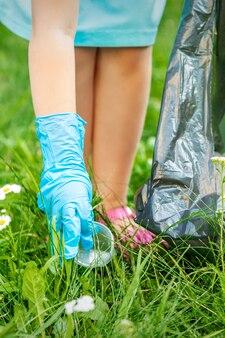 Kind verzamelt plastic afval uit gras gooien afval in vuilniszak in het park