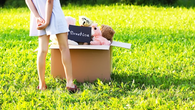Kind verzamelt speelgoed voor het goede doel. zacht speelgoed in kartonnen donatiedoos buitenshuis.
