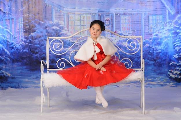 Kind viert kerstmis in de sneeuw op een bankje