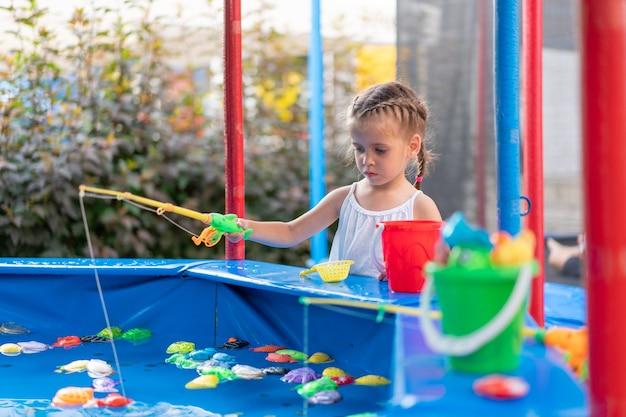 Kind visser vangen plastic speelgoed vis op zwembad pretpark zomerdag meisje veel plezier op vissen carnaval festival entertainment voor kinderen