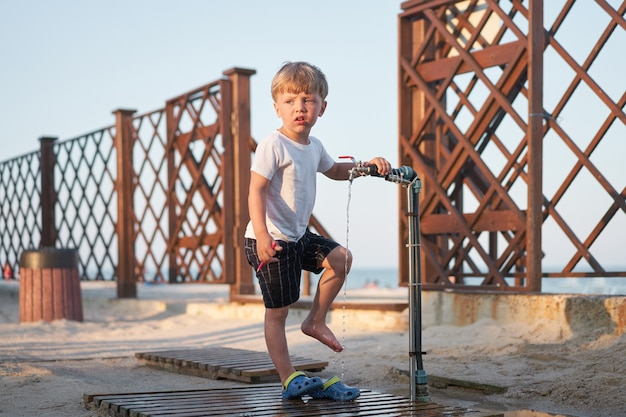 Kind wassen benen na strandzand blanke jongen staande strand. jeugd zomer. familievakantie met één kind.