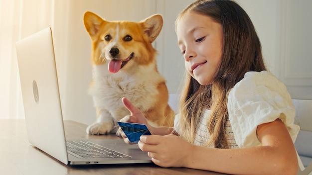 Kind werkt op haar laptop thuis en doet een bewerking met een creditcard.
