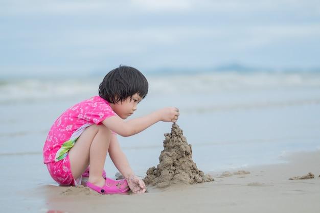 Kind zand spelen op het strand, spelende kinderen in de zee