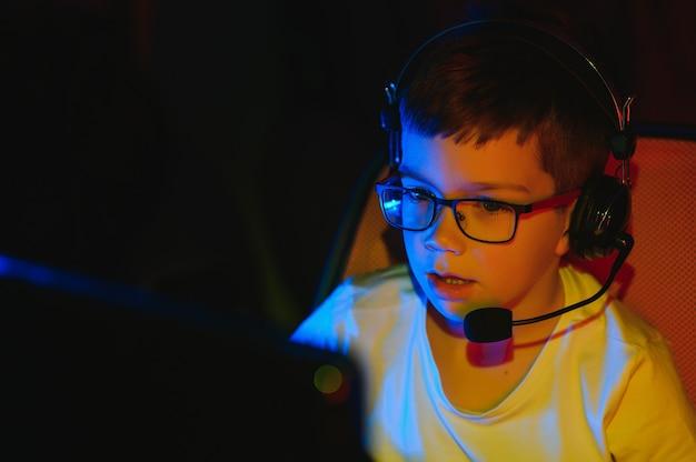 Kind zendt online computerspel uit, jongen streamt in koptelefoon op rgb-verlichtingsachtergrond