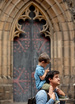 Kind zit op de schouders van zijn vader terwijl hij door de straten van de oude stad loopt