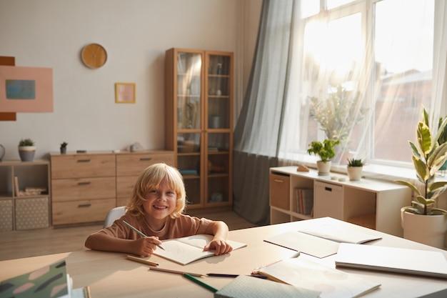Kind zit op zijn werkplek met notebooks en doet zijn huiswerk na school thuis