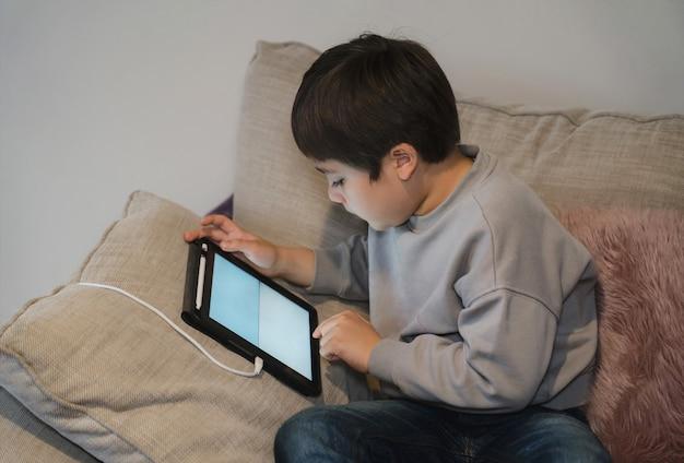 Kind zittend op de bank kijken naar tekenfilms of spel spelen op tablet