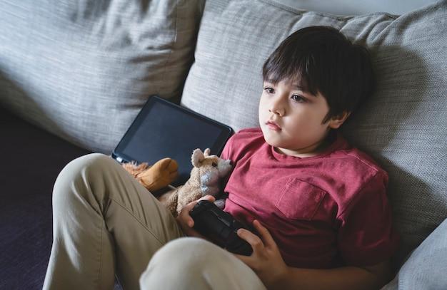 Kind zittend op de bank thuis online spel spelen, kind jongen ontspannen alleen in het weekend