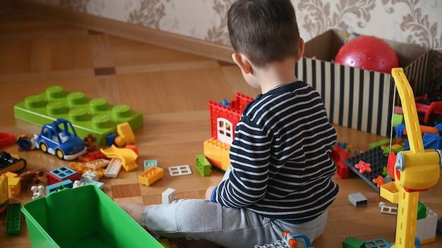 Kind zittend op de vloer speelt constructeur.
