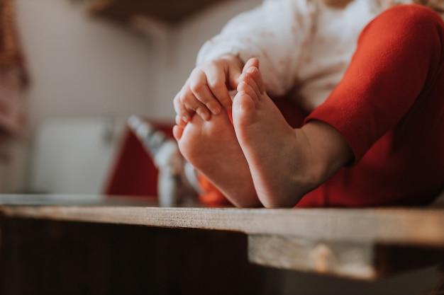 Kind zittend op een houten stoel houdt zijn blote voeten vast met zijn handen ruimte voor tekst