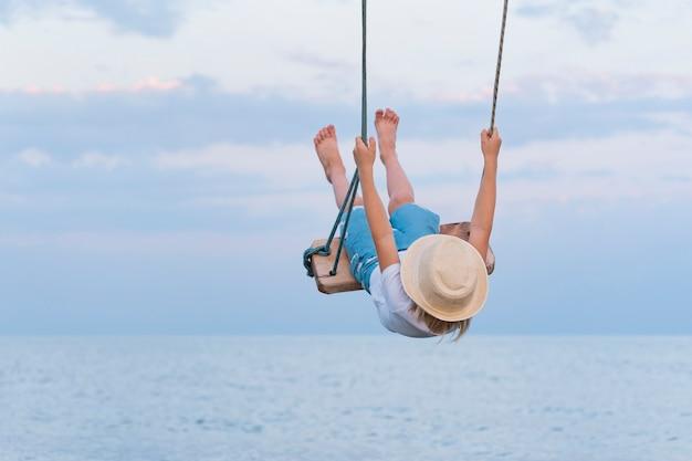 Kind zweeft hoog op schommel. touw slingert over de zee.