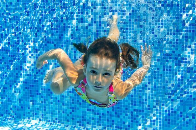 Kind zwemt in het zwembad onder water
