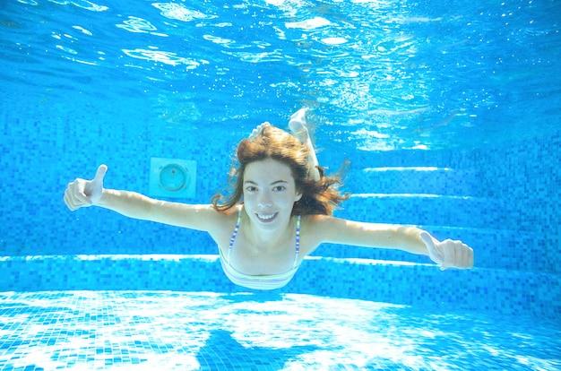 Kind zwemt onder water in zwembad, gelukkig actief tienermeisje duikt en heeft plezier onder water, kindfitness en sport op familievakantie op resort