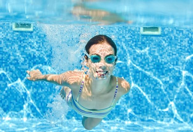 Kind zwemt onder water in zwembad, gelukkig actieve tiener meisje duikt en heeft plezier onder water, kid fitness en sport op familievakantie op resort
