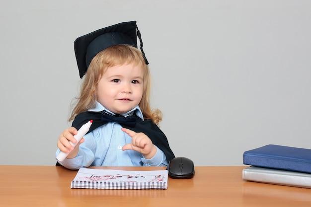 Kindbaby in academische mantel en glb die bij de holdingsmarkering van het school houten bureau zitten