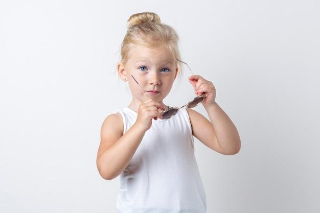 Kindblonde die zich voordeed op een lichte achtergrond in de studio met een zonnebril.