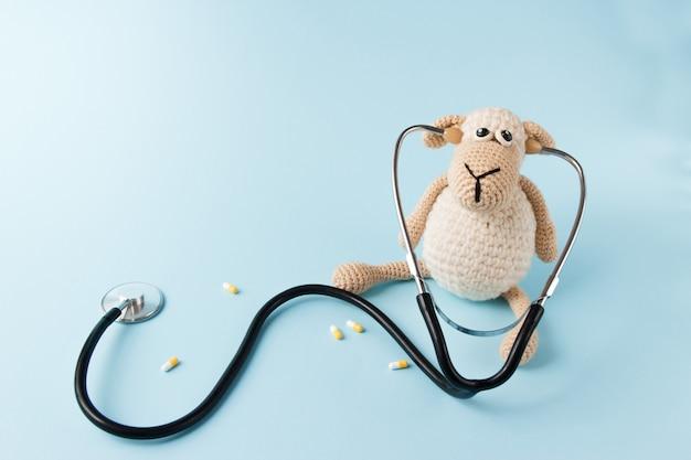 Kinder dokter concept. schapenstuk speelgoed en stethoscoop op blauwe achtergrond