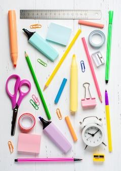 Kinderaccessoires voor studie, creativiteit en kantoorbenodigdheden op een witte houten ondergrond