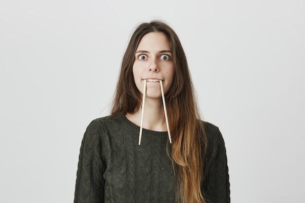 Kinderachtig grappige vrouw in trui houdt chopticks in de mond als dierlijke hoektanden