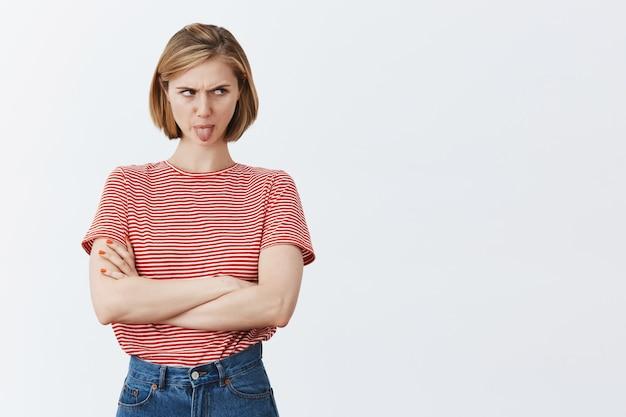 Kinderachtig walgelijk meisje dat tong toont en er goed uitziet gehinderd, uiting geeft aan afkeer