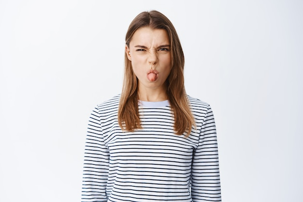 Kinderachtige jonge vrouw die zich smerig gedraagt, tong toont en boos fronst, uiting geeft aan afkeer en minachting, mokkend ontevreden, staande over witte muur