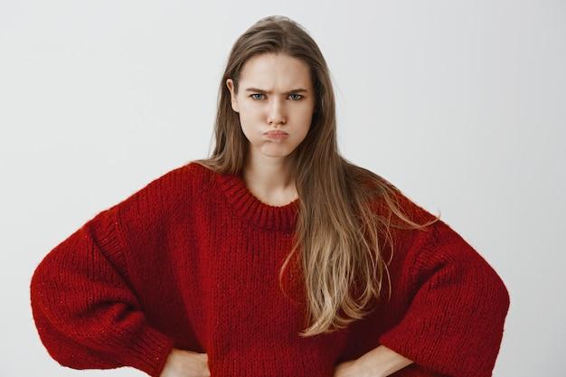 Kinderachtige vriendin wil aandacht. portret van ontevreden beledigde europese vrouw in rode losse trui, hand in hand op heupen, mokkend en fronsend, ruzie makend en beledigd