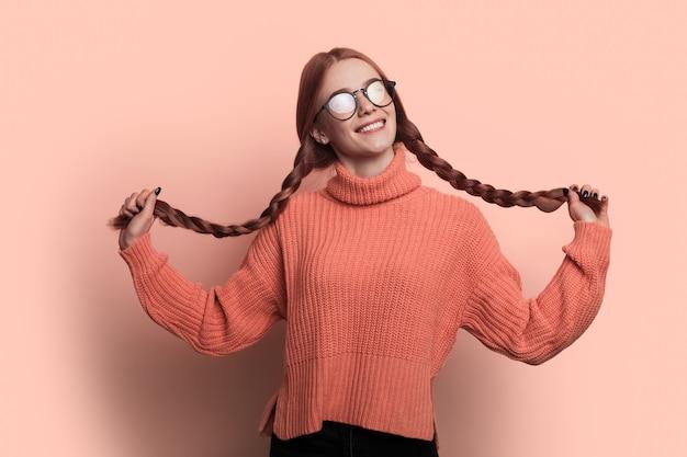 Kinderachtige vrouw met sproeten en rood haar kijkt door een bril
