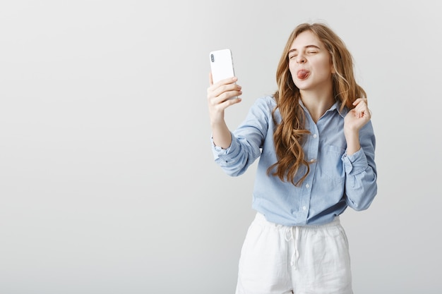 Kinderachtige vrouw praten met minnaar via internet. onbezorgde aantrekkelijke europese vrouw, met smartphone, selfie of videochatten, tong tonen op scherm met positieve houding