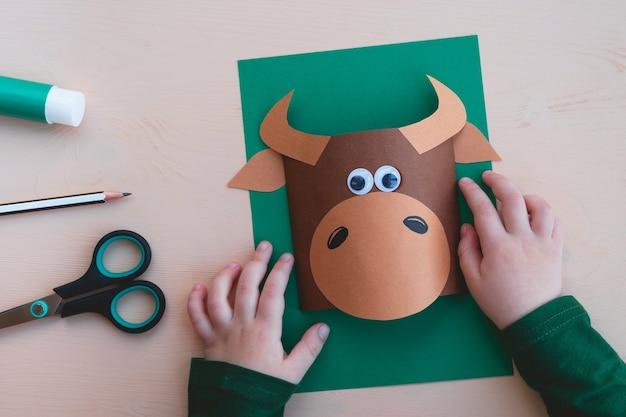 Kinderambachten. kind maakt grappige stier van papier, symbool van het nieuwe jaar 2021. stap 4