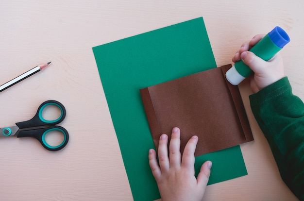 Kinderambachten. kind maakt stier van papier, symbool van het nieuwe jaar 2021. stap 2