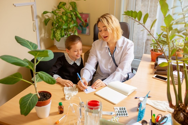 Kinderarts arts behandeling van een kind in comfortabele medische kantoor. gezondheidszorg, jeugd, geneeskunde, bescherming en preventieconcept.
